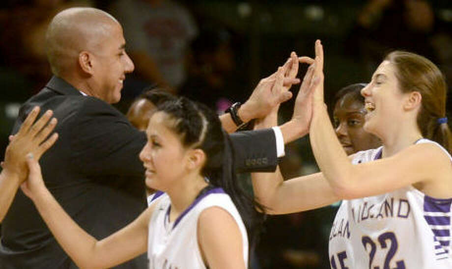 Midland High girls basketball head coach Wes Torres high-fives his players as they come off the court during a time out against Permian's Friday at Chaparral Center. James Durbin/Reporter-Telegram Photo: JAMES DURBIN