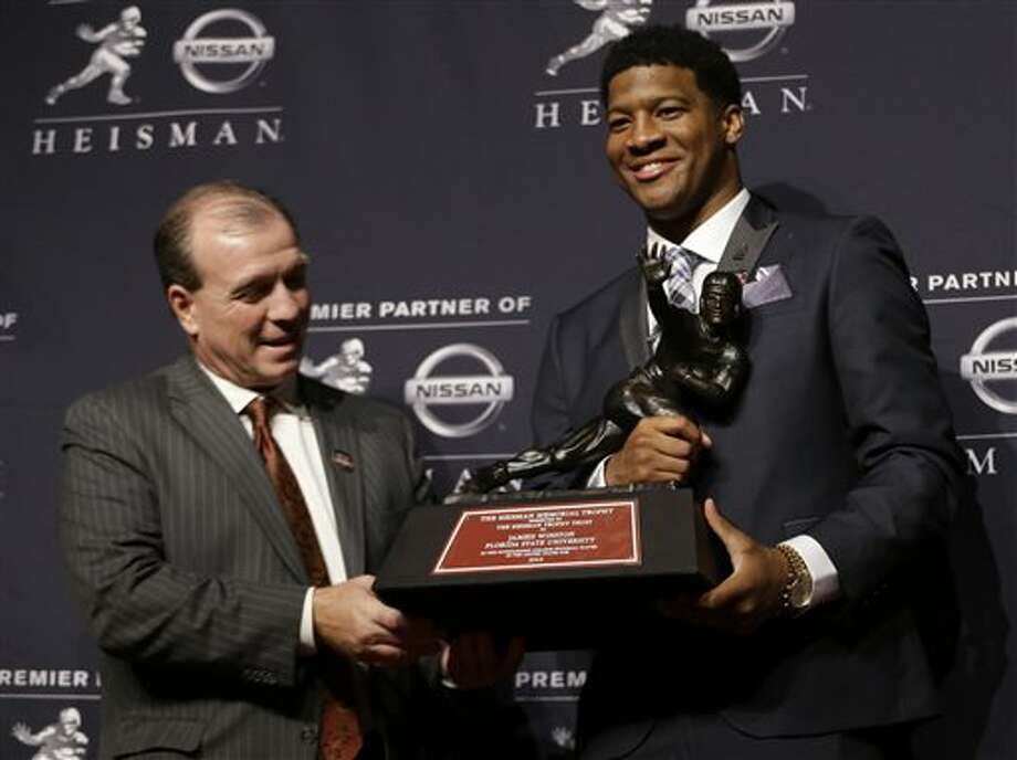 Florida State quarterback Jameis Winston, right, stands with FSU coach Jimbo Fisher while holding the Heisman Trophy after winning the award on Saturday, Dec. 14, 2013, in New York. (AP Photo/Julio Cortez) Photo: Julio Cortez / AP