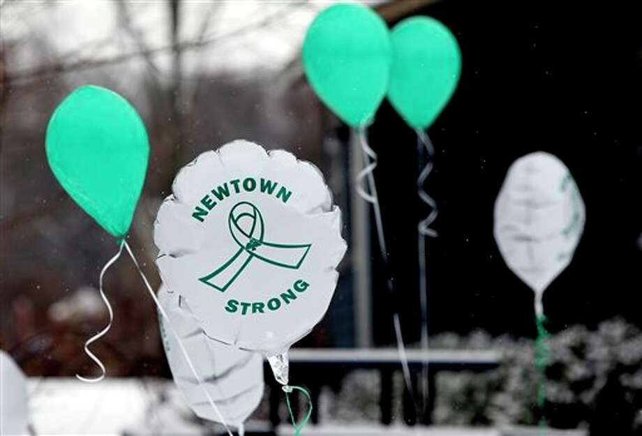 Balloons fly outside a doctor's office on the first anniversary of the Sandy Hook massacre, in Newtown, Conn., Saturday, Dec. 14, 2013. Bells tolled 26 times to honor the children and educators killed one year ago in a shooting rampage at Sandy Hook Elementary School as local churches held memorial services. With snow falling and homes decorated with Christmas lights, Newtown looked every bit the classic New England town. But reminders of the private grief were everywhere. (AP Photo/Robert F. Bukaty) Photo: Robert F. Bukaty / AP