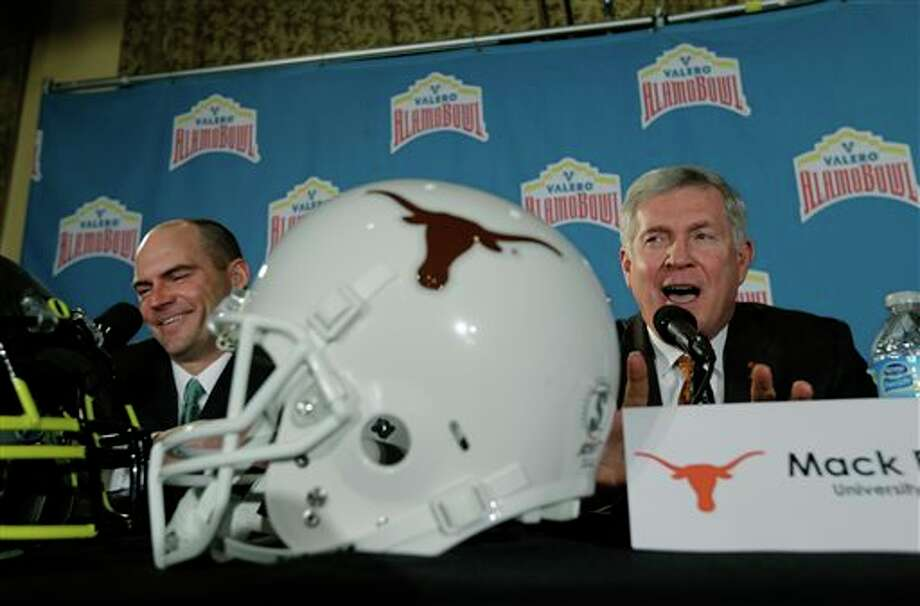 Oregon coach Mark Helfrich, left, and Texas coach Mack Brown, right, take part in a Valero Alamo Bowl news conference, Thursday, Dec. 12, 2013, in San Antonio. Texas and Oregon will play in the NCAA college football game Dec. 30. (AP Photo/Eric Gay) Photo: Eric Gay / AP