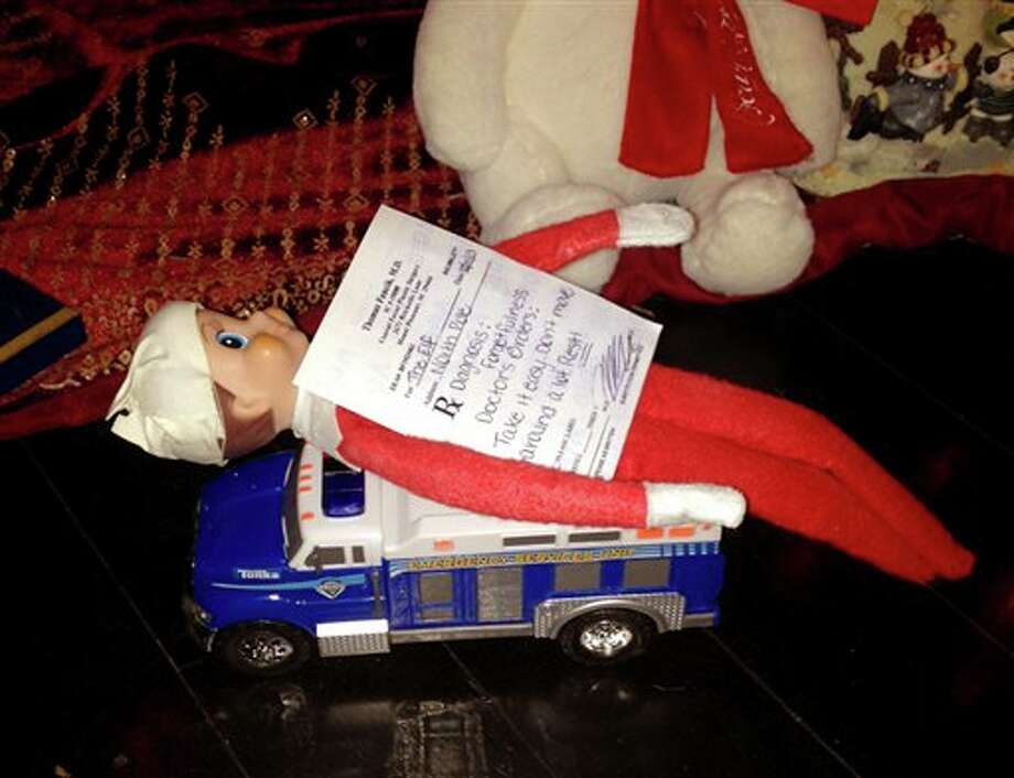 This Dec 11, 2013 photo released by Kim Boerman shows a bandaged elf from the Elf on the Shelf with a prescription by the Christmas tree in the Boerman home in Charleston, S.C. Boerman procured a doctor's prescription after the elf fell from the chandelier during dinner. (AP Photo/Kim Boerman) Photo: Kim Boerman / Kim Boerman