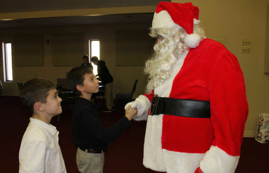 Hillcrest School students Aden Vaughan and Jonathan Cole talk to Santa Clasu dining a Christmas wrapping party at the school Monday. Students and staff from Hillcrest purchased and wrapped gifts for a family of four from Washington Math and Science Institute. Meredith Moriak/Reporter-Telegram