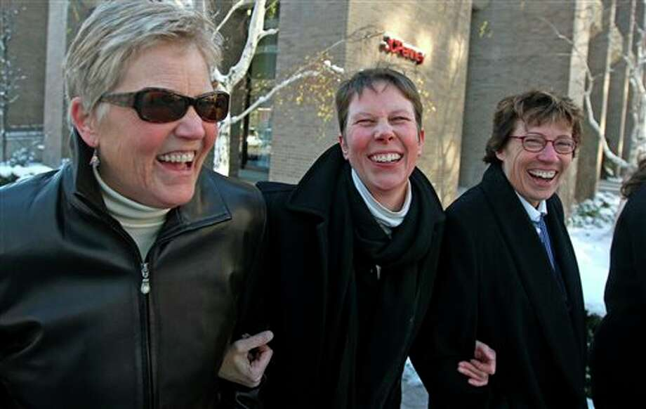 FILE - In this Dec. 4, 2013 file photo, plaintiffs Laurie Wood, left, and her partner, Kody Partridge, center, walk with their attorney Peggy Tomsic after leaving the Frank E. Moss United States Courthouse in Salt Lake City. A federal judge struck down Utah's same-sex marriage ban Friday, Dec. 20, 2013, in a decision that brings a nationwide shift toward allowing gay marriage to a conservative state where the Mormon church has long been against it. (AP Photo/Rick Bowmer, File) Photo: Rick Bowmer / AP
