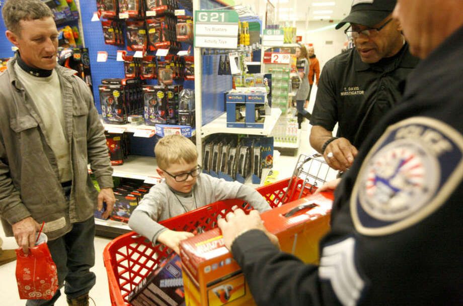 Dawson Baugh, age 9, loads some toys into a shopping cart with his father Steven Baugh, Sheriff's Dept. Investigator Tommy Davis and MPD Sgt. David Scardino during the Shop with a Cop event organized by the Midland Deputy Sheriff's Association on Friday at Target. James Durbin/Reporter-Telegram Photo: JAMES DURBIN