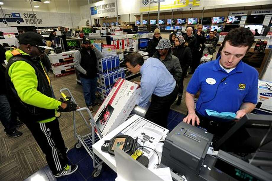 FILE - In this Nov. 29, 2013, file photo, Best Buy employee Christopher Gervais, right, rings up a 32-inch LED TV in Dunwoody, Ga. Sales at U.S. stores dropped 3.1 percent to $42.7 billion for the week that ended on Sunday, Dec. 22, 2013, compared with the same week last year, according to ShopperTrak, which tracks data at 40,000 locations. (AP Photo/David Tulis, File) Photo: David Tulis / FR170493 AP