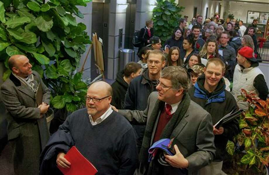 Hundreds of people line up outside of the county clerk's office in the Weber Center on Monday morning, Dec. 23, 2013, the first day that Weber County began accepting applications for same-sex marriage licenses. Couples began lining up outside the building at 10pm on Sunday night due to concern that the state might only issue licenses for one hour before a possible stay could be placed on the ruling that allowed same-sex marriage. (AP Photo/Standard-Examiner, Benjamin Zack) Photo: Benjamin Zack / Standard-Examiner