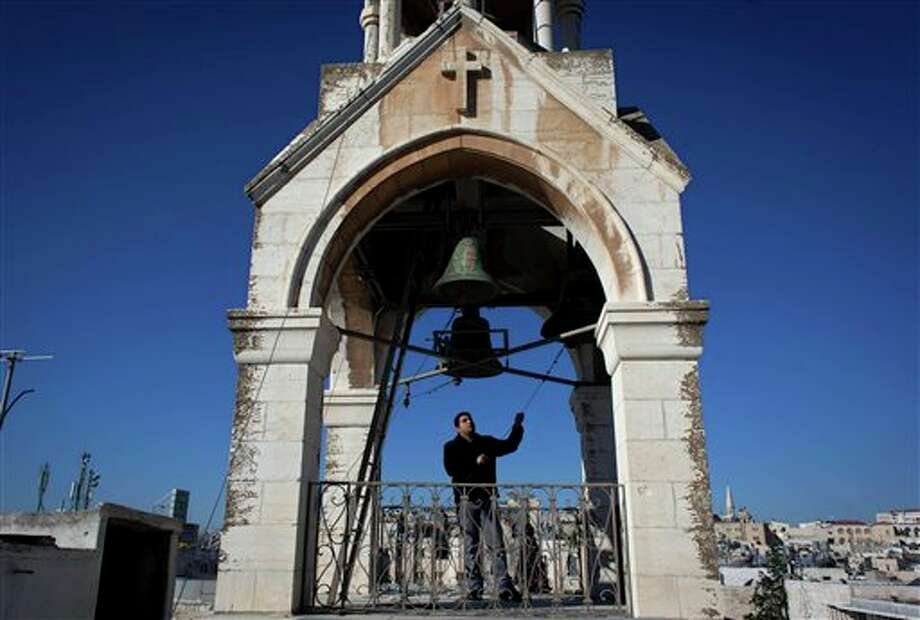 In this photo made Sunday, Dec. 22, 2013, Khadir Jaraiseh, 22, pulls the ropes of four bells in a short tower on the roof of the Church of the Nativity, for prayer services of the Armenian Apostolic Church, in the West Bank city of Bethlehem. The Palestinian college student is one of the last keepers of a fading tradition _ ringing the bells of Bethlehem. Twice a week, he rings the bells a total of 33 times to symbolize the number of years Jesus was believed to have lived. (AP Photo/Nasser Nasser) Photo: Nasser Nasser / AP