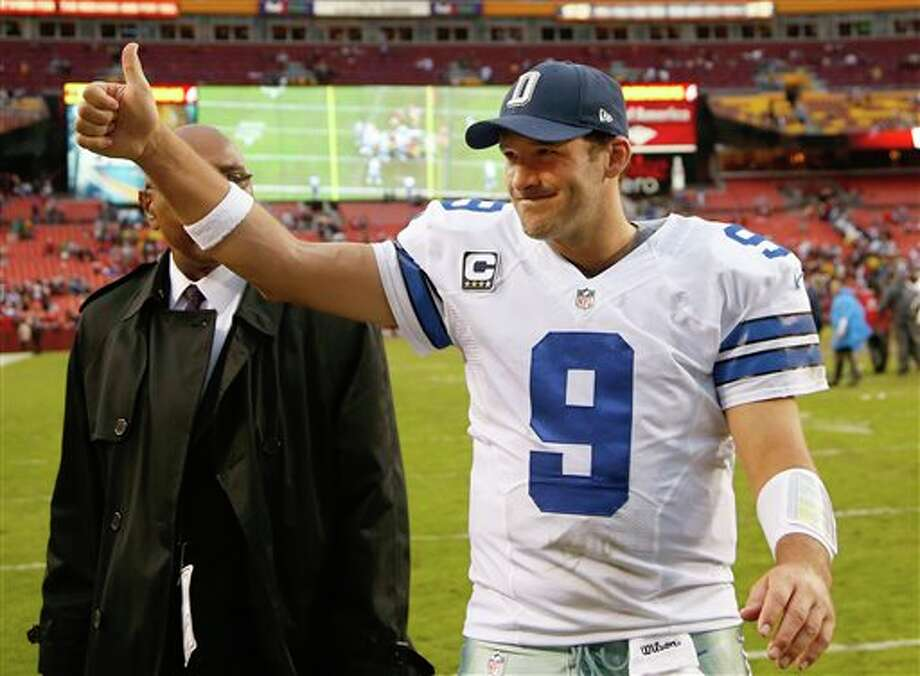 Dallas Cowboys quarterback Tony Romo flashes a thumbs-up as he walks off the field after the Cowboys defeated the Washington Redsksins 24-23 in an NFL football game in Landover, Md., Sunday, Dec. 22, 2013. (AP Photo/Evan Vucci) Photo: Evan Vucci / AP