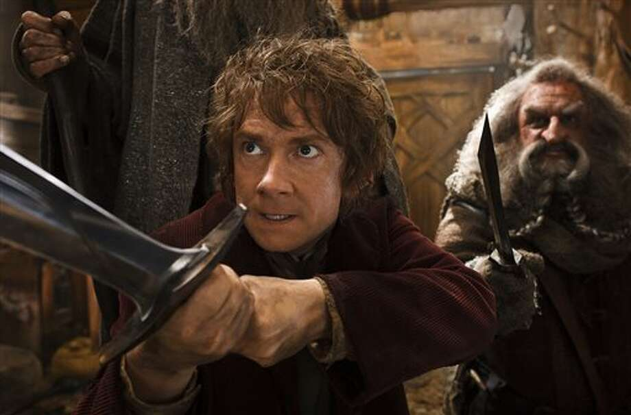 """This image released by Warner Bros. Pictures shows Martin Freeman, left, and John Callen in a scene from """"The Hobbit: The Desolation of Smaug.""""The Hobbit: The Desolation of Smaug"""" continued to top the box office, landing at No. 1 over the Christmas holiday for the third weekend in a row. (AP Photo/Warner Bros. Pictures, Mark Pokorny) Photo: Mark Pokorny / Warner Bros. Pictures"""