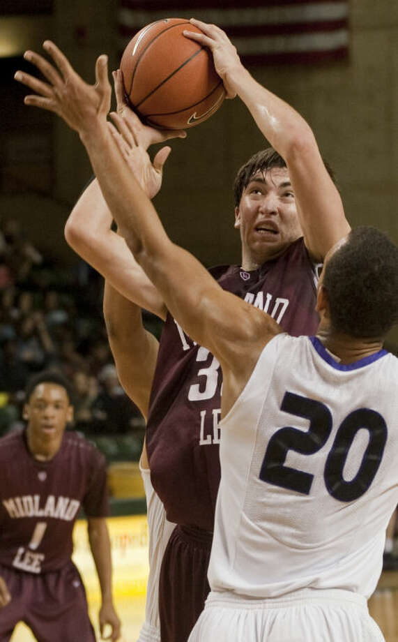 Lee's Jordan Williams drives to the basket and draws the foul from Crowley's Tray Williams, behind, as Markus Jones, 20, defends Saturday in the boys championship game of the Bryon Johnston Holiday Classic in Midland. Tim Fischer\Reporter-Telegram Photo: Tim Fischer