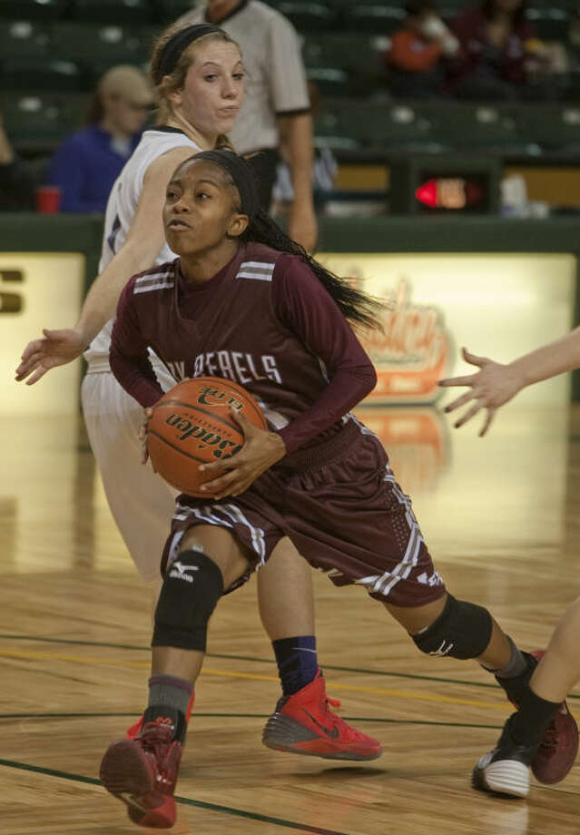 Midland Lee's Daija Stanford drives the lane past Midland Classical's Alissa Beattie Thursday afternoon in the opening game of the Byron Johnston Holiday Classic basketball tournament. Tim Fischer\Reporter-Telegram Photo: Tim Fischer