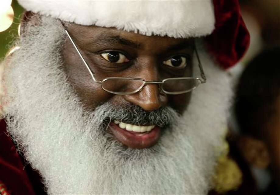 """In this Tuesday, Dec. 17, 2013 photo, Dee Sinclair, portraying Santa Claus, reads a story to children in Atlanta. """"Kids don't see color. They see a fat guy in a red suit giving toys,"""" says Sinclair, 50. (AP Photo/John Bazemore) Photo: John Bazemore / AP"""