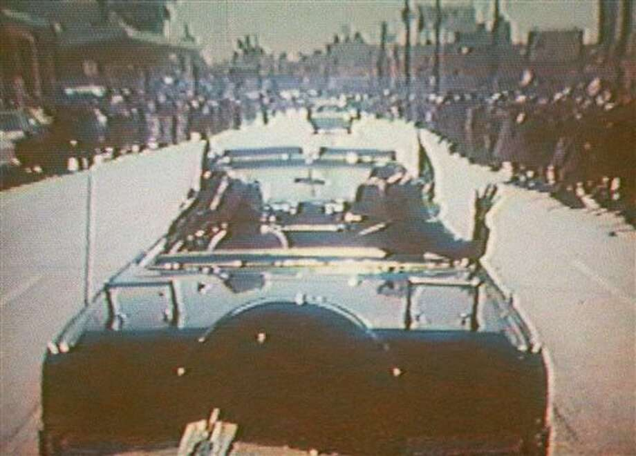 FILE - In this footage taken by presidential aide Dave Powers and photographed from a television screen, President John F. Kennedy, accompanied by his wife, Jacqueline, waves from his limousine in Dallas on Nov. 22, 1963. According to an AP-GfK survey done in April 2013, about 6 in 10 Americans say they believe multiple people were involved in a conspiracy to assassinate President John F, Kennedy, while only one-fourth think Oswald acted alone. Belief in a conspiracy, though strong, has declined since a 2003 Gallup poll found 75 percent said they thought Oswald was part of a wider plot. The Powers film, uncovered by the Assassination Records Review Board and released Thursday, Nov. 21, 1996, shows Kennedy's trip to Texas Nov. 21-22, 1963, prior to the assassination. Powers ran out of film before the motorcade entered Dealey Plaza where the fatal shots where fired. (AP Photo/Assassination Records Review Board, Dave Powers) Photo: Dave Powers / AP1996