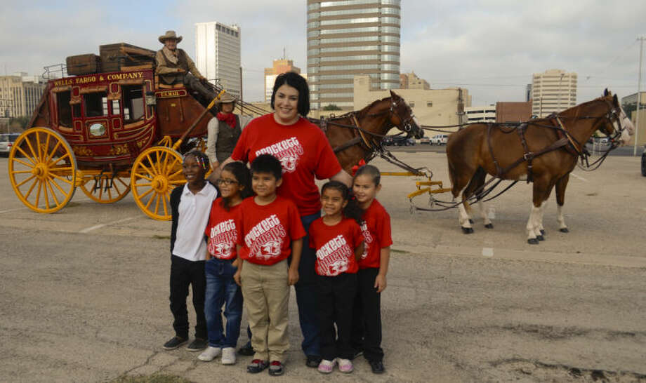 Crockett ELementary Principal Lisa LeClear stands with five of her students, Znieyha Starling, Aalyiah Rodriguez, Steven Garcia, Jazelle Brooks and Sienna Campos Friday morning before they board the Wells Fargo stagecoach to help deliver books to Crockett Elementary first graders. Tim Fischer\Reporter-Telegram Photo: Tim Fischer