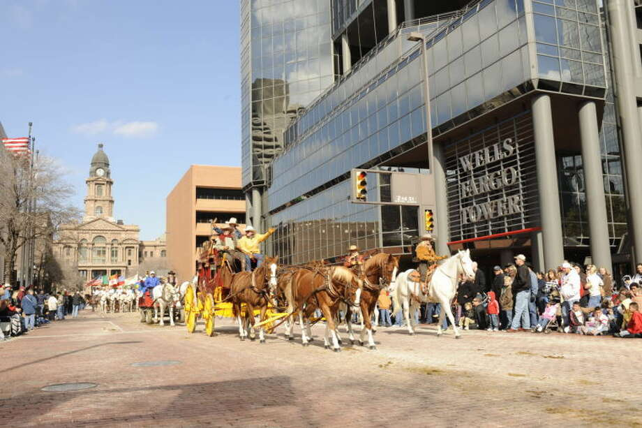 Stagecoach driver Alan Cartwright drives a stagecoach south down Main Street in Fort Worth, with the Tarrant County Courthouse in the background. Cartwright will drive the Wells Fargo stagecoach today as it delivers books to students at Crockett Elementary for the fourth annual Project Literacy donation between Wells Fargo and the Midland Reporter-Telegram. Photo:    Courtesy Photo
