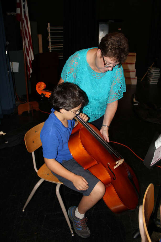 Carver Center strings teacher Lucy Proctor helps fourth grader Aidan Jones tune his cello before class on Sept. 17. Carver expanded its strings program to fourth grade and 23 students are enrolled in the program. Meredith Moriak/Reporter-Telegram
