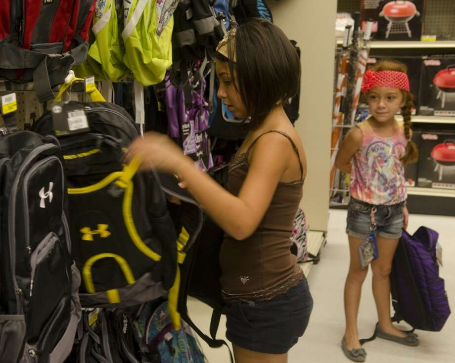 In this Aug. 17, 2012 file photo Tatum Rondan looks at backpacks as her sister, Charlie, already picked one out while shopping at Academy with their mother during tax-free weekend. Photo by Tim Fischer\ Reporter-Telegram Photo: Tim Fischer