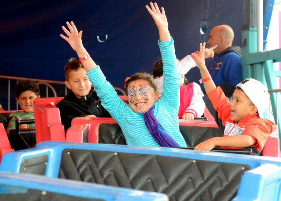 In this September 2012 file photo Rocio and Alejandro Rivera of Midland ride a carnival attraction at the St. Ann's Family Fair. James Durbin/Reporter-Telegram Photo: JAMES DURBIN