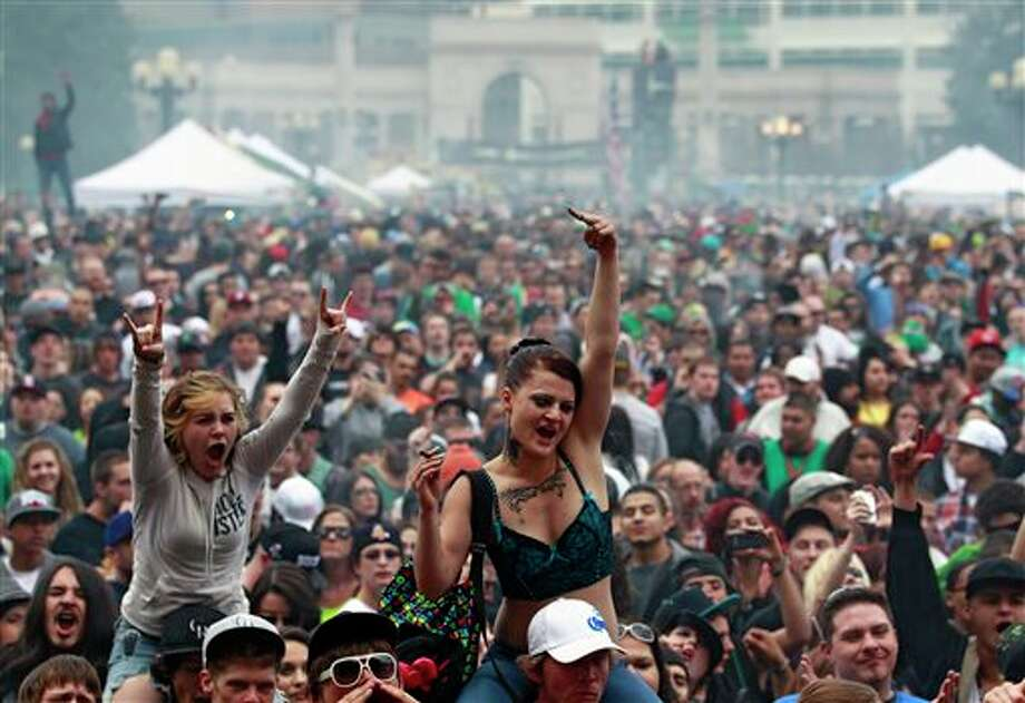 FILE - In this April 20, 2013 file photo, members of a crowd numbering tens of thousands smoke marijuana and listen to live music, at the Denver 420 pro-marijuana rally at Civic Center Park in Denver. The U.S. government said Thursday, Aug. 29, 2013 that the federal government will not make it a priority to block marijuana legalization in Colorado or Washington or close down recreational marijuana stores, so long as the stores abide by state regulations. (AP Photo/Brennan Linsley, File) Photo: Brennan Linsley / AP