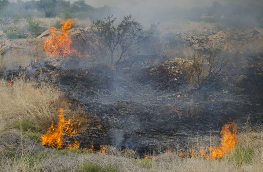 (File Photo) A grass fire burns just south of I-20 Saturday afternoon in a pit near CR 1214. Photo by Tim Fischer/Midland Reporter-Telegram Photo: Tim Fischer