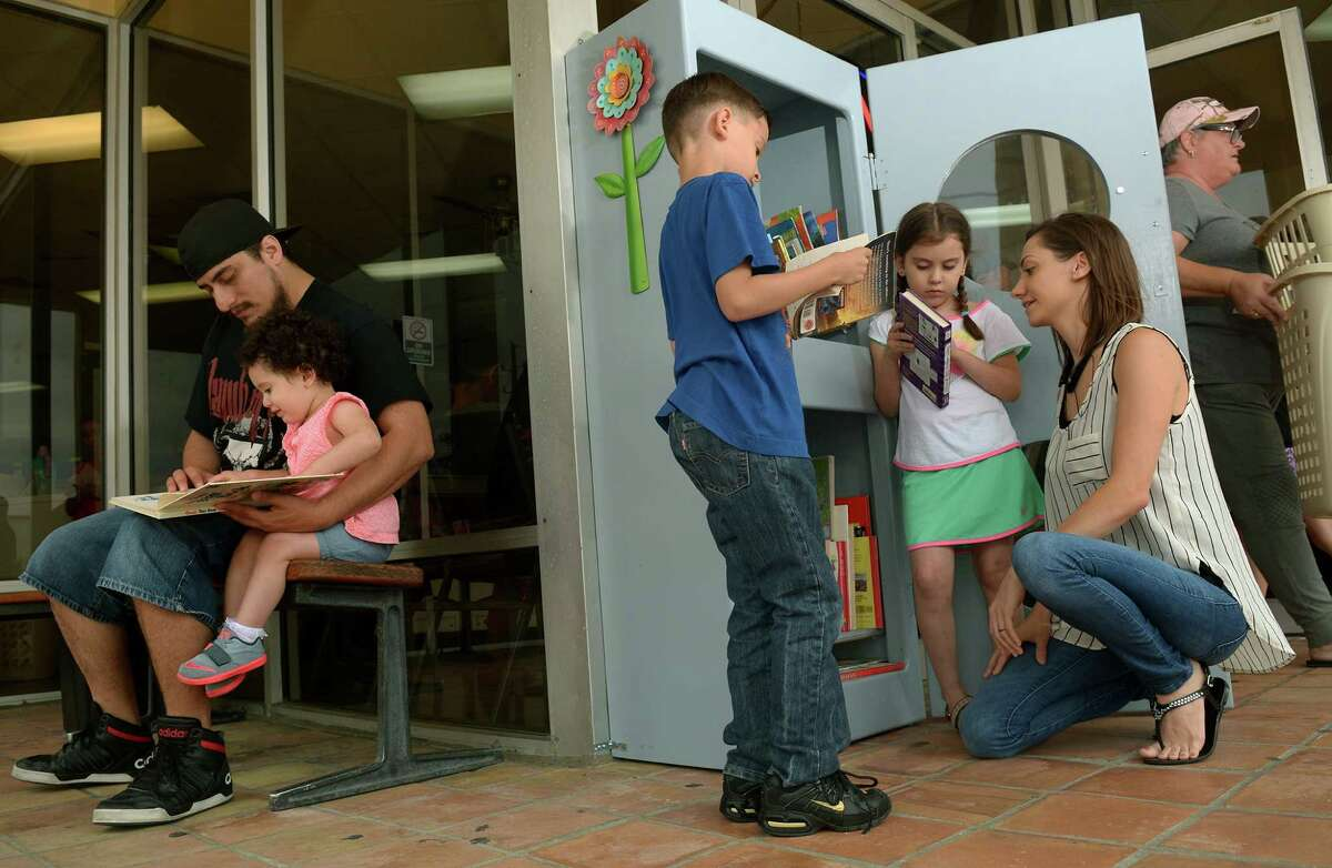 David Aguilar, left, reads a book to daughter Arianna, while son David and daughter, Aliyah, check out books with their mom Michelle Aguilar in the Little Free Library in front of the Kingwood Laundromat.