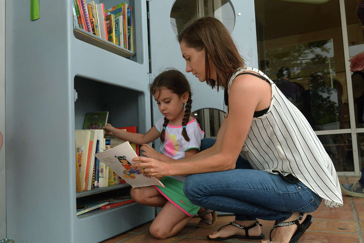 Aliyah Aguilar, 5, left, checks out a book with her mom, Michelle, at the Little Free Library owned by Brenda Williams in front of the Kingwood Laundromat, also owned by Williams.