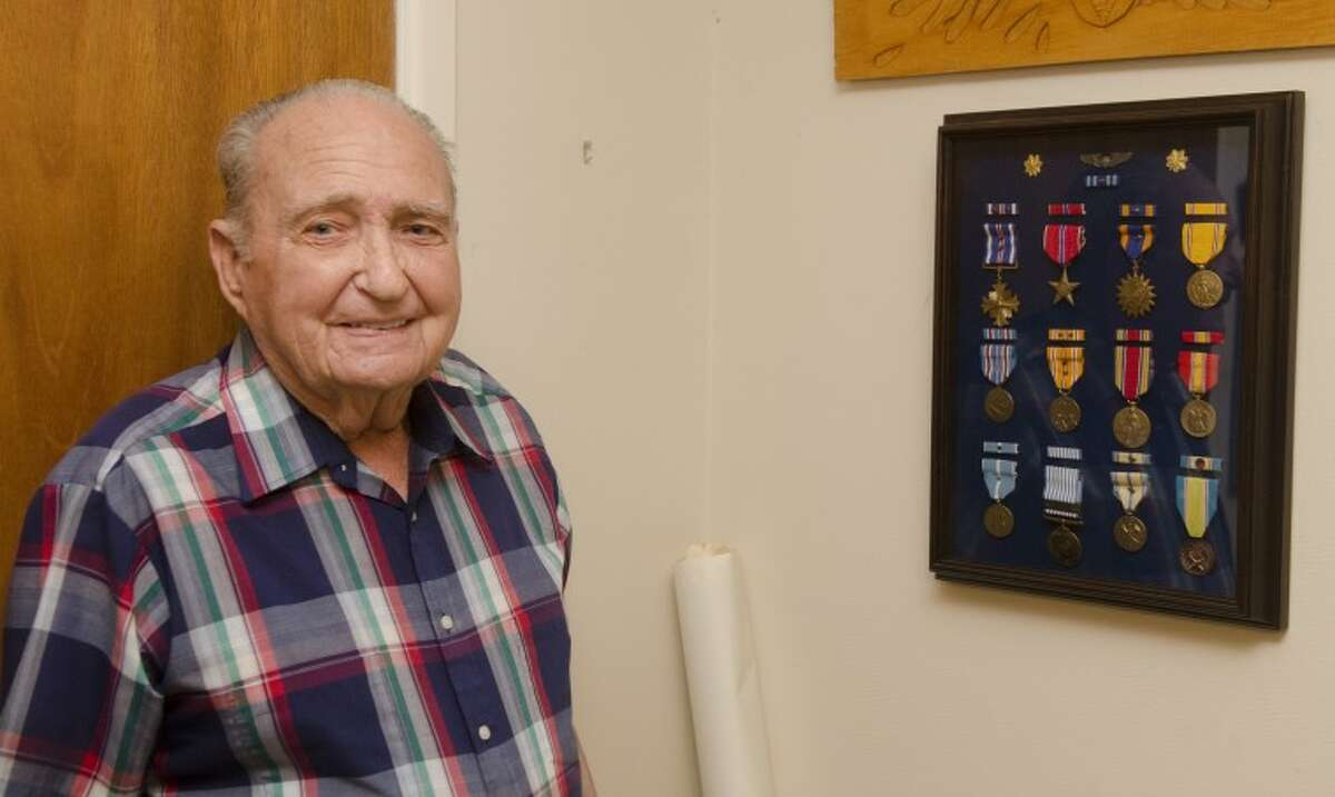Donad Troy stands with his case of medals from WWII and Korea. Photo by Tim Fischer/Midland Reporter-Telegram