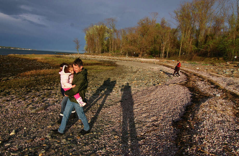 """The Connecticut Audubon Society Coastal Center at Milford Point held a walking tour of the Charles Island on Wednesday April 28, 2010. Here, Andreas Zaugg, of Milford, carries his daughter Maria, 6, along the beginning of an exposed tombolo as he leaves the Charles Island tour. A tombolo is a small bridge of land that connects an island to the mainland. This one gets exposed at low tide so the island can be accessed by foot. About 25 people gathered for this tour. Another """"Charles Island Exploration"""" event is planned for May 14th from 5:45 to 7:15 p.m.. For more information call the center at 1 (203) 878-7440. Photo: Christian Abraham / ST / Connecticut Post"""