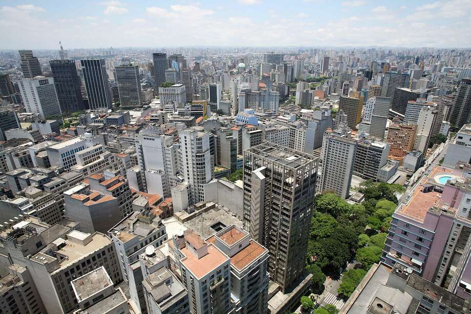Apartment and office buildings clutter the skyline of Sao Paulo, Brazil, where a new policy creates permits to allow con struction of taller buildings. The city auctions these certificates to developers, with the revenue going to infrastructure. Photo: ANDREW HARRER, BLOOMBERG NEWS