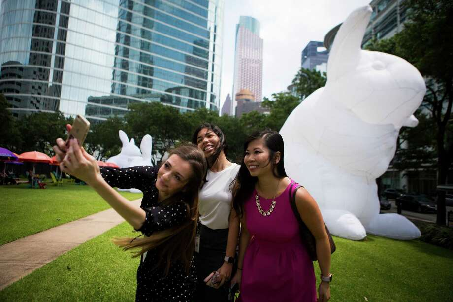 """(left to right) Virjinia Hadjieva, Erika Arredondo, and Wynne Chan gather for a selfie by Australian artist Amanda Parer's monumental installation """"Intrude"""" in downtown Houston, Tuesday, May 10, 2016, in Houston. The ladies walked a block to take a closer look at the bunnies and for photos. ( Marie D. De Jesus / Houston Chronicle ) Photo: Marie D. De Jesus, Staff / © 2016 Houston Chronicle"""