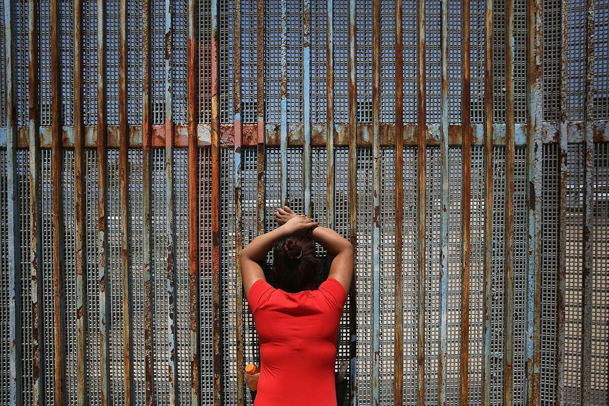 """TIJUANA, MEXICO - MAY 01: Gabriella Ramirez, 23, speaks to her boyfriend, a construction worker who immigrated to California, through the U.S.-Mexico border fence on May 1, 2016 in Tijuana, Mexico. Mexicans on the Tijuana side can approach the border fence at any time. The U.S. Border Patrol, however, tightly controls the San Diego, CA side and allows visitors to speak to loved ones through the fence during restricted weekend hours at """"Friendship Park"""". The park is the only place along the 1,954-mile border where such interactions are permitted by U.S. authorities. On only three occassions have U.S. officials allowed a gate to be opened at the park for pre-screened separated family members to embrace. (Photo by John Moore/Getty Images)"""