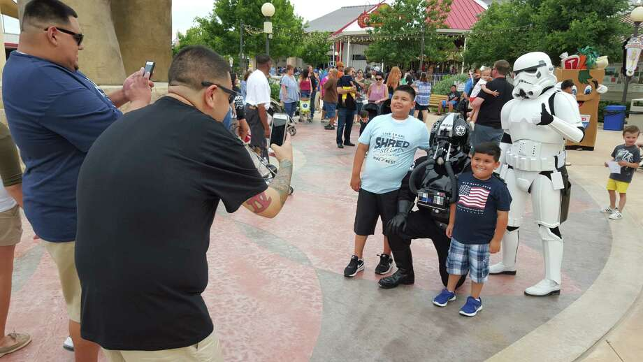 Jesse Q. Gonzales III, left, and Jimmie Criollo, far left, snap photos of their sons, Jagger Criollo, 9, and Jesse Q. Gonzales IV, 5, far right, with Star Wars stormtroopers. The families accompanied Criollo's daughter, Jaylen, to Morgan's Wonderland was a Make-A-Wish recipient in 2012. Photo: Jeff B. Flinn / NE Herald