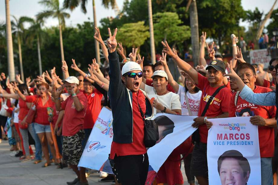 "Supporters of Ferdinand Marcos Jr. flash the ""V"" sign as they shout support at a Manila park. Photo: TED ALJIBE, AFP/Getty Images"
