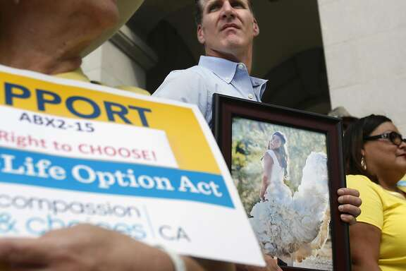 Dan Diaz holds a photo of his late wife, Brittany Maynard during a rally calling for California Gov. Jerry Brown to sign the right to die legislation at the Capitol in Sacramento, Calif., Thursday, Sept. 24, 2015. Maynard was the 29-year-old California woman with brain cancer who moved to Oregon to legally end her life. The measure, approved by both houses of the Legislature, faces an uncertain future with Brown, a former Jesuit seminarian who has not said whether he will sign it. (AP Photo/Rich Pedroncelli)