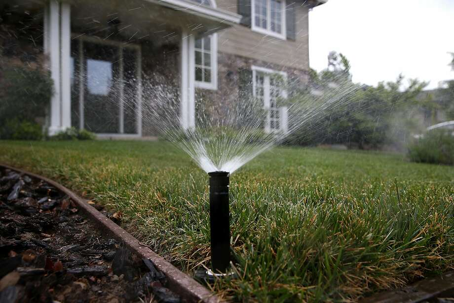 "A sprinkler waters a lawn on April 7, 2015 in Walnut Creek, California. On a 7-0 vote, the East Bay Municipal Utility District board ruled on Tuesday that water supply levels were ""normal,"" suspended water rationing and also dropped the 25 percent drought surcharge on water bills, effective July 1. Photo: Justin Sullivan, Getty Images"