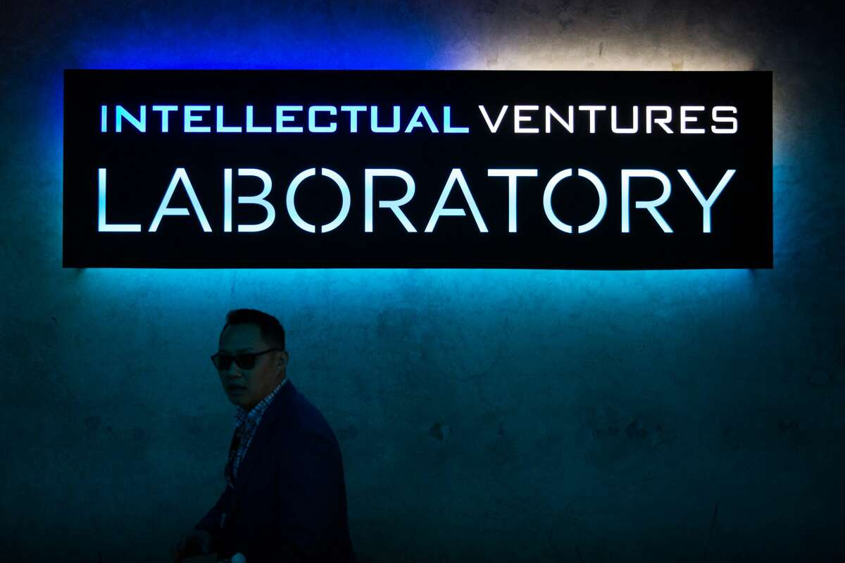 Paul C. Cabellon walks under a sign in the lobby of the Intellectual Ventures laboratory in Bellevue on Wednesday, May 4, 2016.