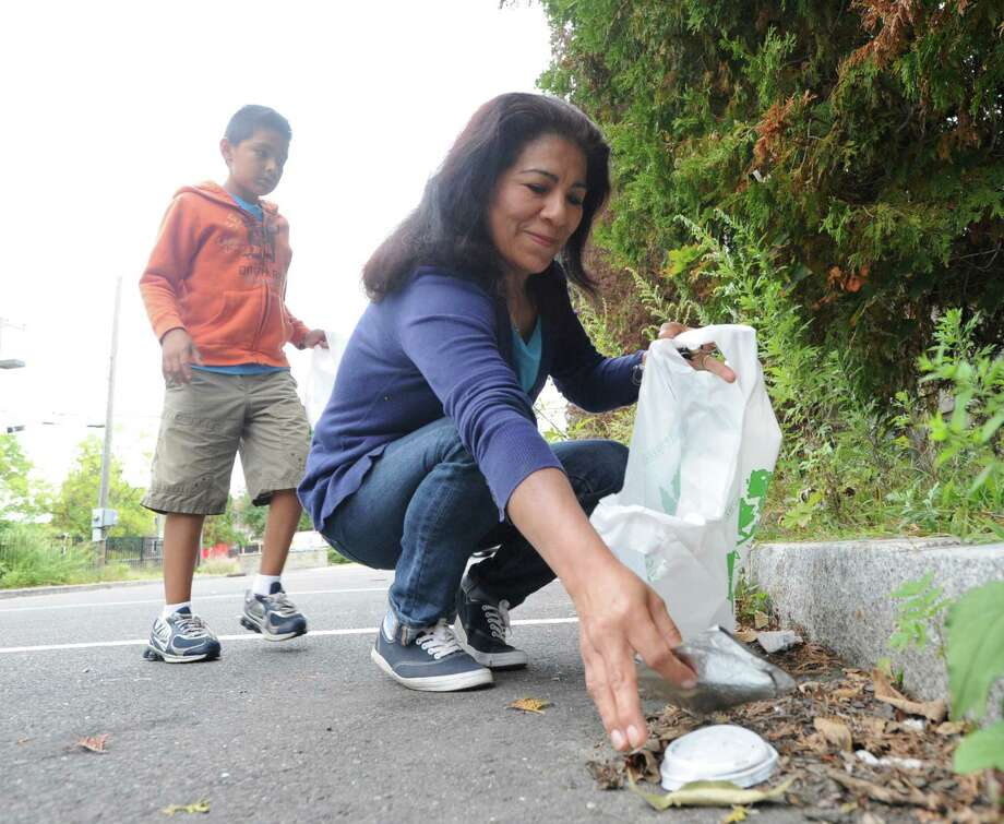 Bertha Ramos, right, and her son, David DaSilva, 8, of Greenwich, bag trash in the parking lot at the Cos Cob School during the Greenwich Clean & Green annual town-wide fall cleanup. The organization's spring cleanup will take place on Saturday, May 14. Photo: Bob Luckey / Bob Luckey / Greenwich Time