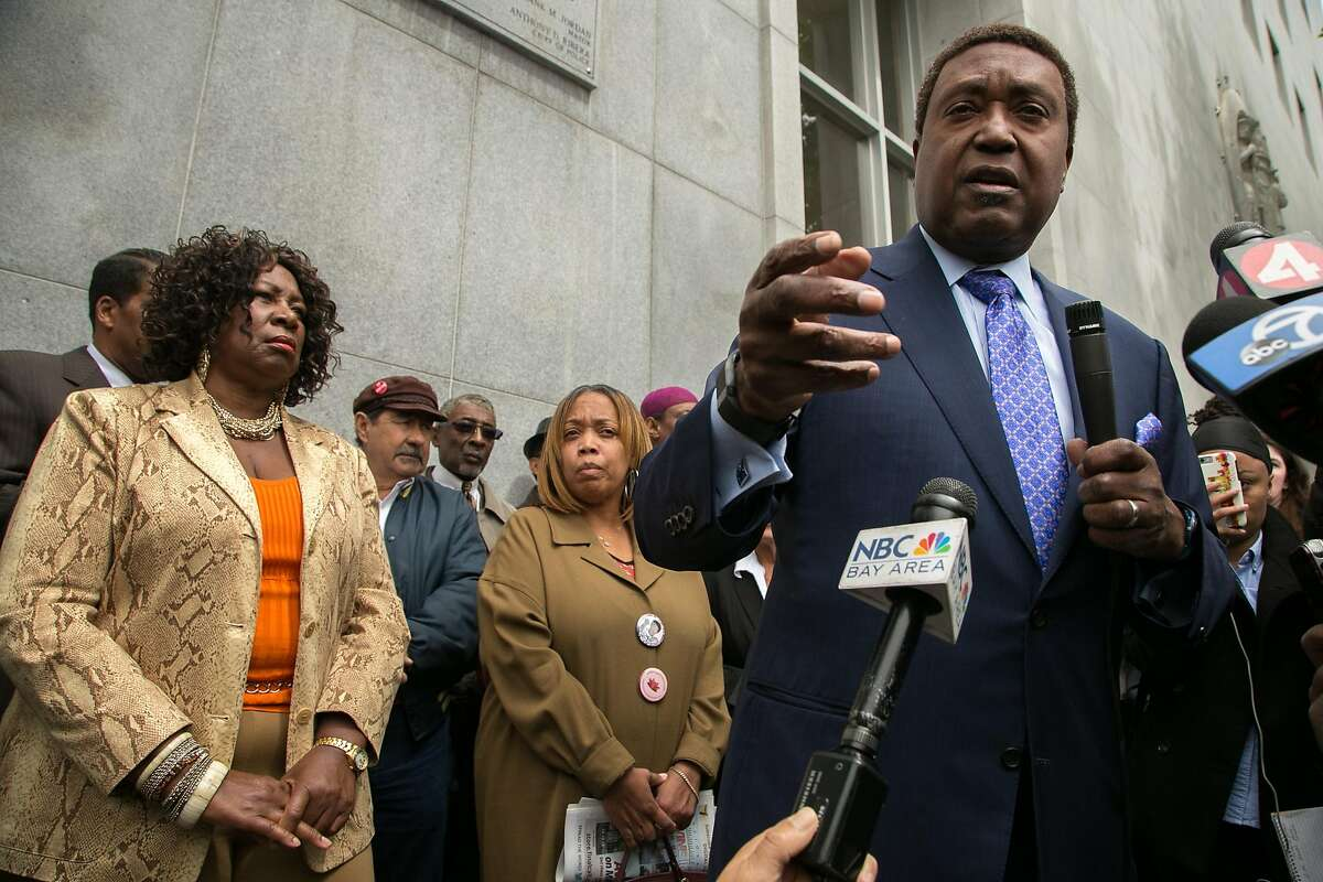 Civil rights attorney John Burris speaks to members of the media before a news conference outside the Hall of Justice on Wednesday, May 11, 2016 in San Francisco, Calif. Felicia Jones, left, with the Justice 4 Mario Woods Coalition, and Woods' mother Gwen are seen in the background.