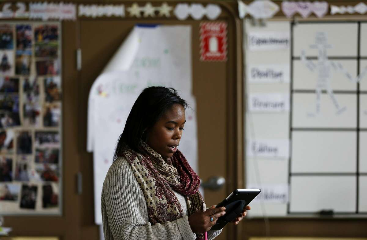 Kamaria Carnes of Teach for America reads off a tablet during her 8th grade English Language Arts class at Everett Middle School in San Francisco, California, on Wednesday, May 11, 2016.