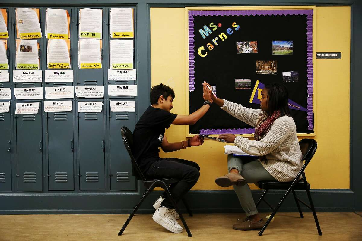 Kamaria Carnes (right) of Teach for America high-fives Anderson Agular after he finishes an oral exam during her 8th grade English Language Arts class at Everett Middle School in San Francisco, California, on Wednesday, May 11, 2016.