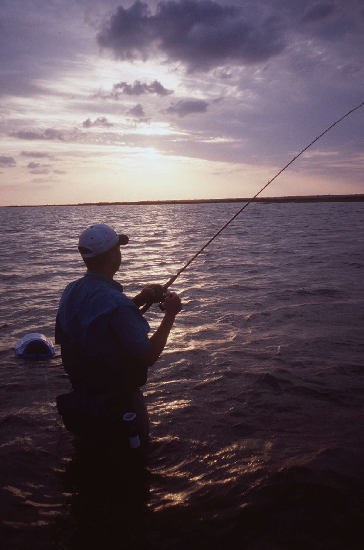 Texas Coast fishing. (v) Wade fishing the bayside flats is easily accessed on the back side of Mustang Island, home of Port Aransas. The hard-sand bottom is relatively free of structure, making the walking comfortable. Photo by Ron Henry Strait, staff. April 2002.
