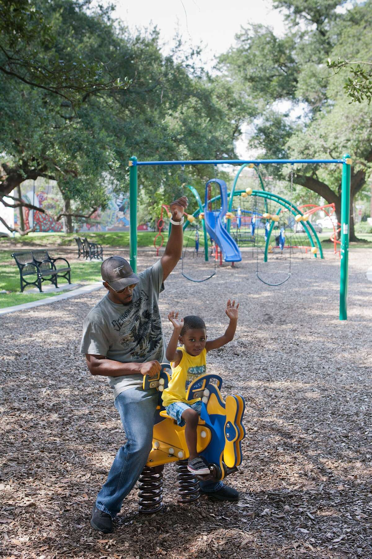 Ty Williams and his son Porter Williams, 3, enjoy the new playground in Baldwin Park on Elgin in Midtown. Porter was all about being an airplane today. Photo By R. Clayton McKee
