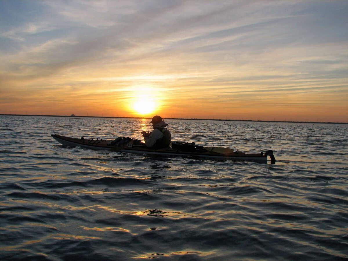 A photo of colin mcdonald in his kayak at sunset. Taken on colin McDonald's kayak trip along the texas gulf coast. Photo credit TK