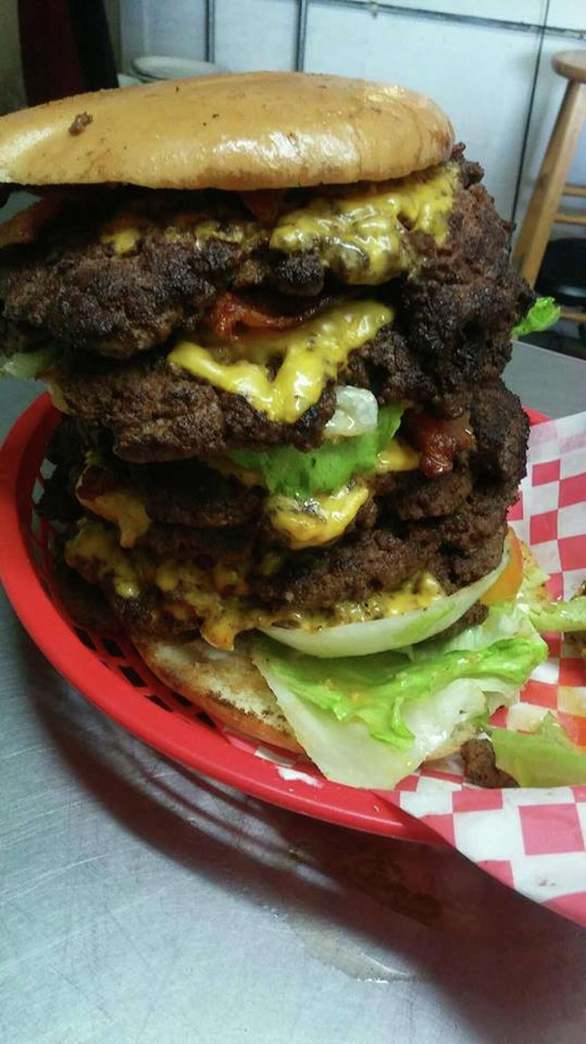 """The """"Boban Burger"""" is a colossus with six patties and onion rings, owner Raymond Diaz said he has yet to see anyone finish."""