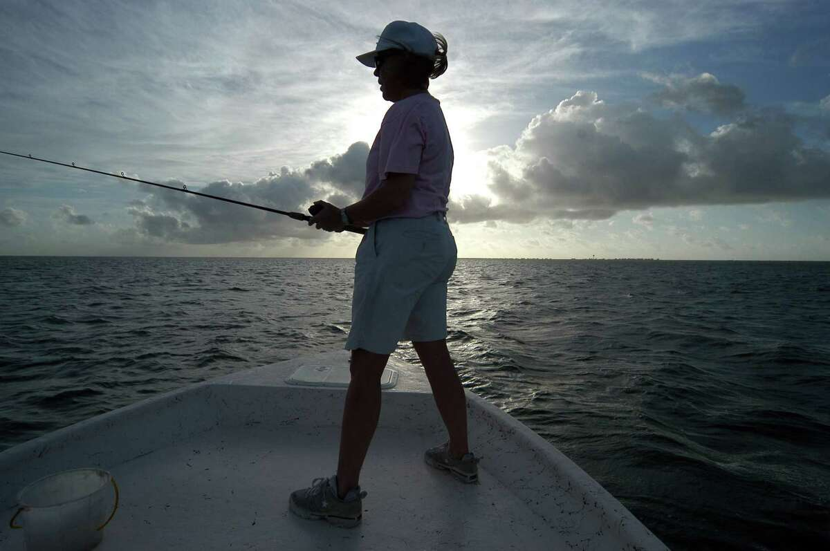 Susan Cooley, Ph.D., R.N., project director for Reach Out & Read Texas and assistant professor of pediatrics at The University of Texas Medical School at Houston, competes during an All-Girl Fishing Tournament at Pirates Beach Marina at sunrise in Galveston June 12, 2004. Carlos Javier Sanchez/Special to the Chronicle. HOUCHRON CAPTION (07/09/2004): In the First Annual Galveston Bay All-Girls Fishing Tournament, competitors fish a little differently from men - they have more fun. HOUCHRON CAPTION (07/11/2004): Fishing is about loving the water, as well as reeling in a big one, and Susan Cooley, casting off the bow of a boat owned by Hook Set Charters' Capt. Chris Jamail, decided to share the experience by creating an all-women's fishing tournament.