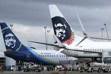 FILE - In this Monday, April 4, 2016, file photo, Alaska Airlines planes with the company's new livery and tail logo, left, and the old livery used to promote service to Hawaii, right, are shown parked at Seattle-Tacoma International Airport in Seattle. Alaska Airlines and JetBlue Airways still rank highest in the annual J.D. Power survey of passengers on the nine largest North American airlines, and the firm says overall traveler satisfaction with the industry is at a 10-year high. J.D. Power said Wednesday, May 11, 2016, that Alaska ranked highest among traditional airlines for the ninth straight year and JetBlue was the top-rated low-cost carrier for the 11th year in a row. (AP Photo/Ted S. Warren, File)