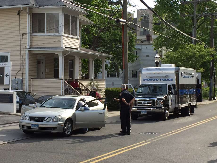 Stamford police search a car near the corner of North and Franklin streets Wednesday afternoon. Photo: Michael Cummo / Hearst Connecticut Media