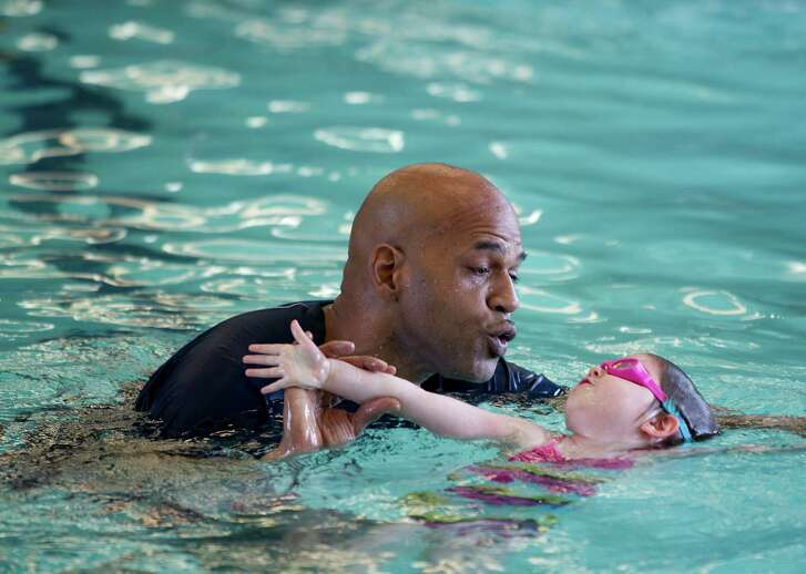 Swim instructor Chrivas Pritchett works with 4-year-old Mia Lutz, at Sharpstown Pool.