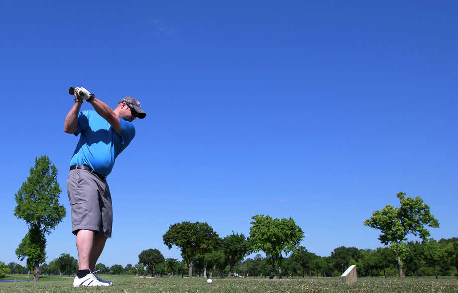 Blue skies provide a backdrop for Jonathan Heard as he prepares to hit a golfball at Bear Creek Park. Photo: Cody Duty, Staff / © 2015 Houston Chronicle