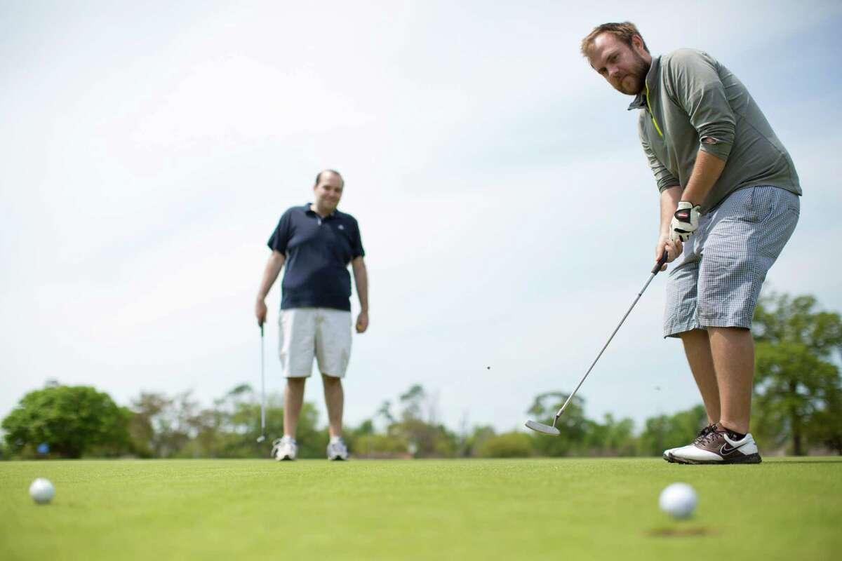 Travis King putts an under par at Gus Wortham Park Golf Course hole 16 with Robert Bravman.